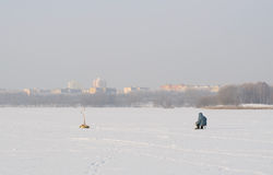 Zamarznięty jezioro w mieście z rybakiem na tle domy i kościół obrazy royalty free