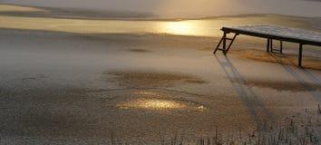 Zamarznięty jezioro w słońce promieniach i molo przy zmierzchem Zdjęcie Stock