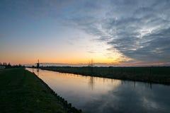 Zamarznięty kanał w Holandia z wiatraczkiem na horyzoncie przy zmierzchem zdjęcia stock