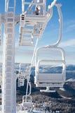 Zamarznięty krzesła dźwignięcie przy śnieżnym kurortem w zim górach na pogodnym da Fotografia Royalty Free