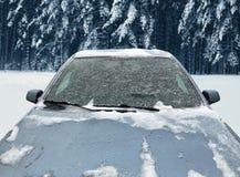 Zamarznięty samochód zakrywający zima śnieg, przegląda frontowego okno przednią szybę i kapiszon na śnieżnym obrazy stock