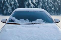 Zamarznięty samochód zakrywający zima śnieg, przegląda frontowego okno przednią szybę i kapiszon na śnieżnym lesie obraz stock