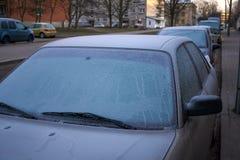 Zamarznięci samochodowi okno, wczesny poranek na miasto ulicach Fotografia Stock