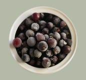 Zamarznięte jagody, czarni rodzynki w porcelany naczyniu, na widok Makro- Zdjęcie Stock