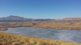Zamarznięty jezioro pod skalistymi górami zdjęcia royalty free