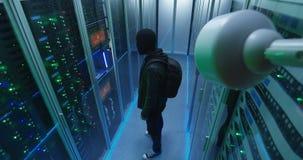 Zamaskowany hacker z jego laptopem budzi się przez serweru wiosłuje zdjęcie wideo