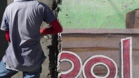 Zamaskowany męski budowa kamieniarza rzutów cement na ścianie zbiory