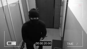 Zamaskowany rabusia wybuch przez drzwi i łamał kamerę bezpieczeństwa z opony żelazem Zdjęcia Stock