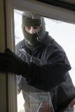 Zamaskowany złodzieja łamanie Wewnątrz Przez okno zdjęcie stock