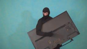 Zamaskowany złodzieja Balaclava który kraść TV i patrzeje zmęczonym zbiory wideo