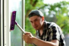 Zamazana ostrość młodego człowieka cleaning okno z kwaczem Nadokienna płuczka Fachowa cleaning firma obraz stock
