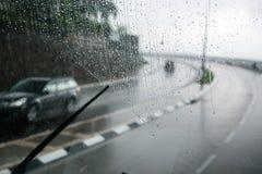 Zamazana uliczna scena przez samochodowych okno z deszcz kroplą Zdjęcia Royalty Free
