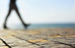 Zamazanej mężczyzna sylwetki againts chodzący nadmorski obraz stock