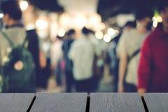 Zamazani ludzie chodzi tło i drewnianego stół na chrzcielnicie mock zdjęcie stock