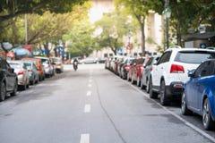 Zamazani samochody parkujący na miastowej ulicie popierają kogoś fotografia royalty free