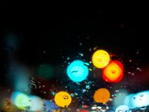 Zamazany deszcz opuszcza teksturę na samochodowym okno z kolorowego bokeh abstrakcjonistycznym tłem na drodze zdjęcia stock