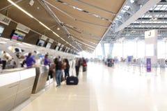 Zamazany lotniskowy sprawdza wewnątrz biurko kontuaru bramę z ważącym bagażu paskiem zdjęcie stock