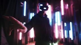 Zamazany mężczyzna jest ubranym VR słuchawki w neonowych światłach zbiory wideo
