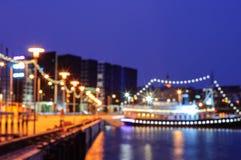 Zamazany nocy miasta tło z łodzią na molu Obraz Stock
