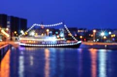Zamazany nocy miasta tło z łodzią na molu Zdjęcie Stock