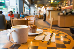 Zamazany peple, filiżanka coffe z mupfin tortem Zdjęcia Royalty Free