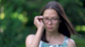 Zamazany portret azjatykcia kobieta stawia up jej szkła Ostrość pojawiać się po stawiać na szkłach Zieleni drzewa na zbiory wideo
