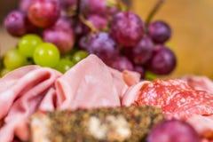 Zamazany przedpole i tło wciąż życie kolor żółty, czerwony muszkatołowy winogrono, ser i salami -, - zdjęcie royalty free