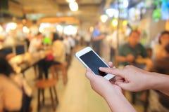 Zamazany ręki i dotyka ekranu mądrze telefon na ludziach w jedzenia cen zdjęcia stock
