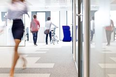 Zamazany ruch bizneswomanu odprowadzenie z męskimi kolegami w tle przy biurem zdjęcia stock