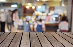 Zamazany wizerunku drewna stół i jedzenie ześrodkowywamy przy zakupy centrum handlowym i pe Fotografia Stock