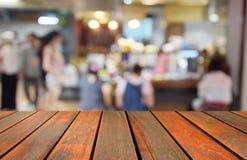 Zamazany wizerunku drewna stół i jedzenie ześrodkowywamy przy zakupy centrum handlowym i pe Fotografia Royalty Free