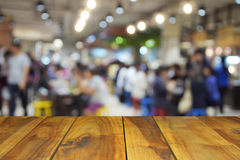 Zamazany wizerunku drewna stół i jedzenie ześrodkowywamy przy zakupy centrum handlowym i pe Zdjęcie Stock