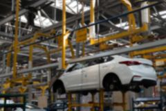 zamazuj?cy t?o Budowa samochody w fabryce Biały samochód bez kół na dźwignięciu Przemysłowa pojazd linia produkcyjna zdjęcie stock