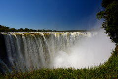 Zambesi river and Victoria Falls. Zimbabwe. Victoria Falls, or Mosi-oa-Tunya (the Smoke that Thunders), is a waterfall in southern Africa on the Zambezi River at Royalty Free Stock Photo