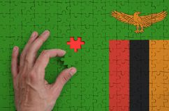 Zambia flag is depicted on a puzzle, which the man`s hand completes to fold.  vector illustration