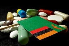 Zambiaanse vlag met partij van medische die pillen op zwarte backgro wordt geïsoleerd Royalty-vrije Stock Foto's