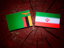 Zambian flag with Iranian flag on a tree stump isolated Royalty Free Stock Photos