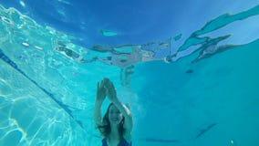Zambulliéndose, la hembra sonriente en el traje de baño está flotando debajo del agua con los ojos abiertos en piscina pura metrajes