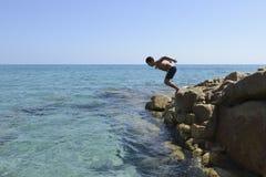 Zambullida del muchacho en el mar Fotos de archivo