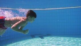 Zambullida del muchacho en piscina almacen de video