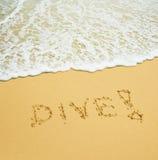 Zambullida escrita en una playa tropical arenosa Foto de archivo