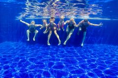 Zambullida feliz de la familia en piscina foto de archivo