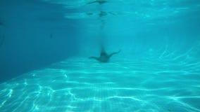 Zambullidas blancas de la muchacha en piscina azul y nadadas a la c?mara Visi?n de debajo el agua almacen de video