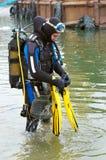Zambullidor de equipo de submarinismo que entra en el agua Imagen de archivo