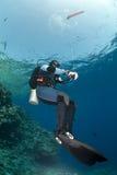 Zambullidor de equipo de submarinismo que sostiene una boya superficial de la etiqueta de plástico. Foto de archivo