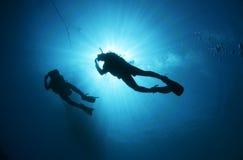 Zambullidor de equipo de submarinismo silueteado contra el sol Imágenes de archivo libres de regalías