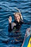 Zambullidor femenino feliz en agua al lado del barco Imagen de archivo