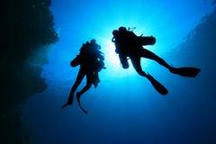 Zambullidores de equipo de submarinismo silueteados Imágenes de archivo libres de regalías