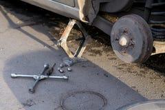 Zamieniać tylni koło samochód Samochód wspina się na Jack Na śrubach, narzędziu i kole drogowych kłamstwa, fotografia royalty free