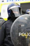 Zamieszka funkcjonariusz policji z osłoną i hełmem Zdjęcia Royalty Free